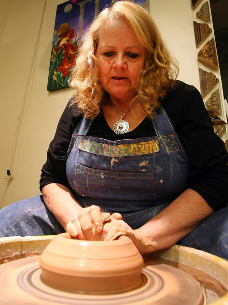 Linda Rimstidt Coward works on a pice of pottery at her downtown studio located in the Courtyard by Marriott Atlas Life Building lobby