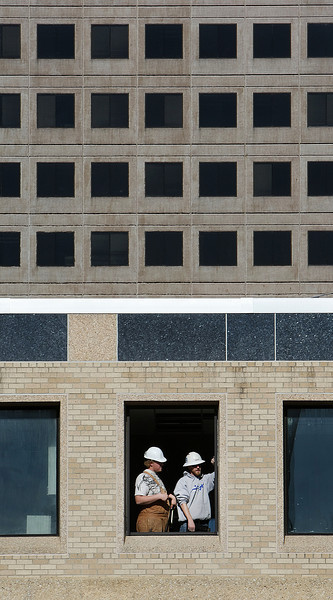 Workmen install a window at the Warren Clinic Springer Building in South Tulsa.