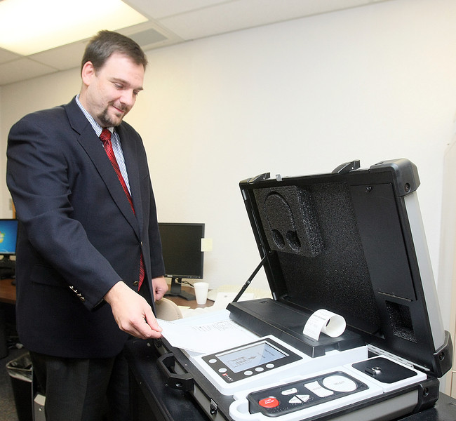 Paul Ziriax, secretary of the state election board, scans a ballott into the eScan A-T voting machine. PHOTO BY MAIKE SABOLICH