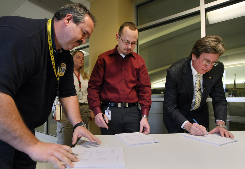 Twenty Six year 911 Dispatcher Shawn Aarington, Michael Rider AFSCME President and Tulsa Mayor Dewey Bartlett sign a contract raising the dispatchers wages.