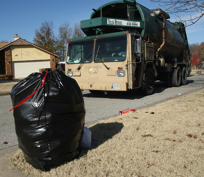 Derosa Boyd and Emmanuel Tino pick up household trash on their route in South Tulsa. Tulsa's trash board has a busy week beginning Monday, facing a lawsuit in Tulsa District Court on Monday and a possible vote on Tuesday by the Tulsa City Council to get the OK to borrow $17 million for trash carts.