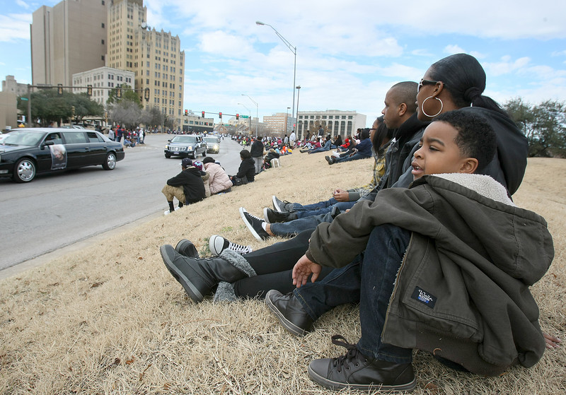 The Maxwell family watches the Martin Luther King Jr. parade through downtown Monday.  Jalen sits is the fron. PHOTO BY MAIKE SABOLICH