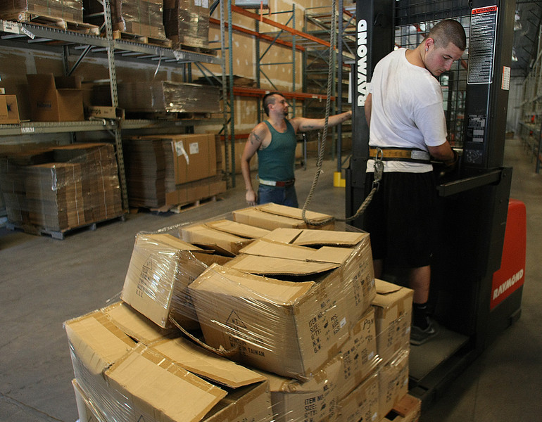 Valhoma employees Keving Peterson and Braden Robinson move stock onto the warehouse shelves in their new warehouse in Tulsa.