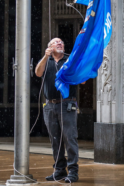 During a sudden afternoon downpour security takes down the Oklahoma flag, after takeing American flag, at the First National Building.