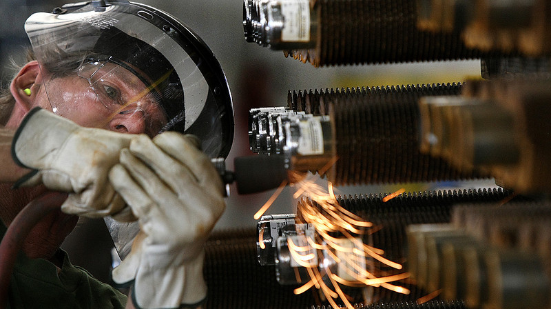 Fintube employee Jessie Gerry grinds heat exchanger tubes to a smooth finish at the companies Tulsa manufacturing facility.