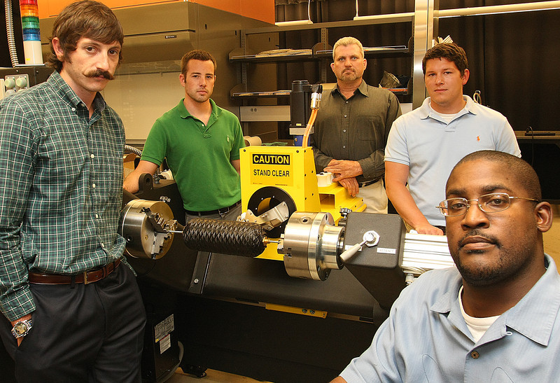 Co-Owners of CleanNG Jake Crawley, Michael Tate, Aaron Laney, Matt Villareal and Nate Waters pause for a photo with the prototype of the compressed gas canister they are developing.
