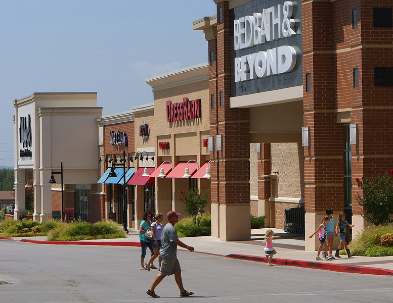 Shoppers walk to the shops at the Tulsa Hills Shopping Center.