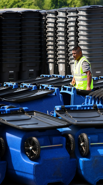 A workman is surrounded by new trash cans he is assembling before being distributed to Tulsa Residents.