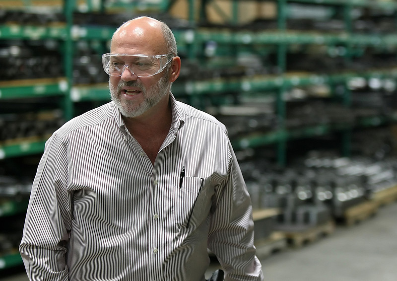 Dale Fain, President & CEO of Team Oil Tools, walks past shelves holding spare parts for products tmanufactured in the Tulsa plant.