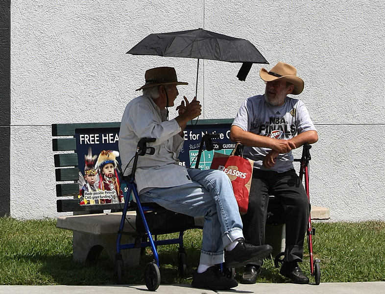Jose and Tony use a small unbrella for shade as they wait in the Pearl District of Tulsa for their bus to arrive.