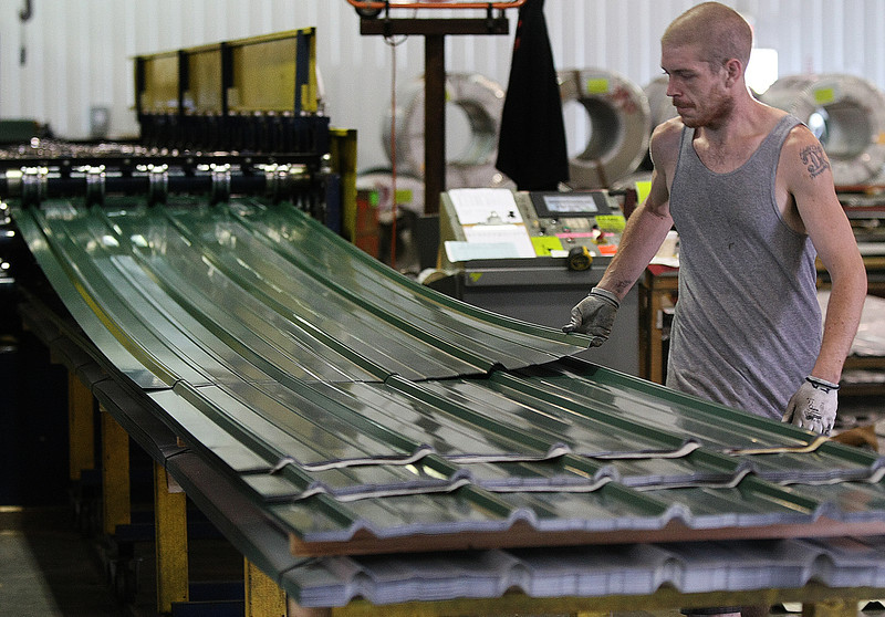 Ed Hammond stacks metal panels as they exit the roller press at Metal Panels Inc.