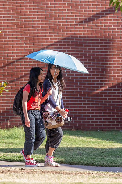 Two students shade themselves from the sun on a hot afternoon at UCO in Edmond.