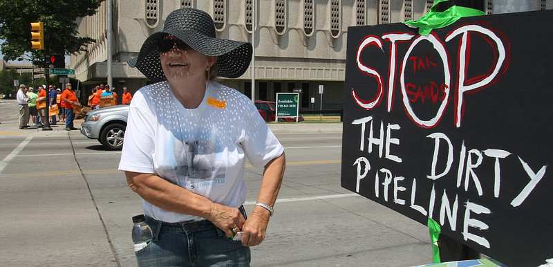 Jean McMahon, an opponent of the Keystone pipeline, tapes a sign to a pole in downtown Tulsa while demonstrating against the project.