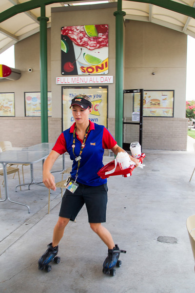 Skating car-hop Jamie delivers lunch at the Sonic located on Shariden and Classen.