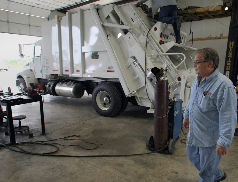 Wayne Fields, President Waste Research Inc. strolls past a back end loading trash truck similar to the type being rushed to completion for Tulsa collections.