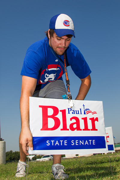 Josh Blair, son of canidate Paul Blair, places campaign sign on Lincoln Blvd in front of the Oklahoma County Election Board.