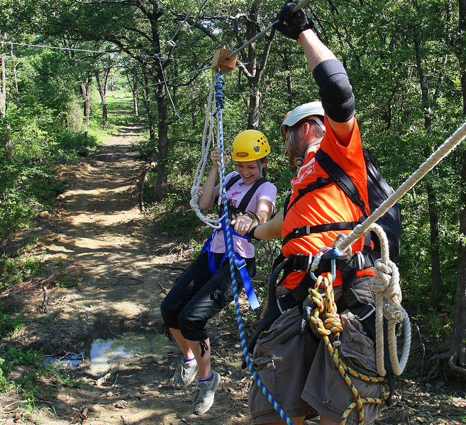 At the bottom the zip line course Abbie Alford get an assist onto the platform from a staff member of the at the Post Oaks Lodge in Tulsa.