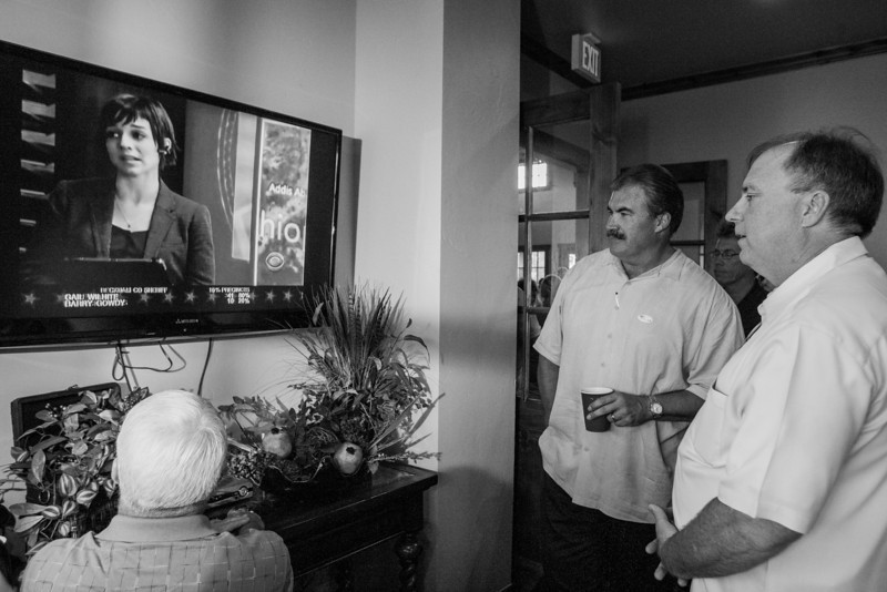 Surrounded by supporters Paul Blair watches TV for election results at his watch party held at the Iron Horse neihbor hood clubhouse.