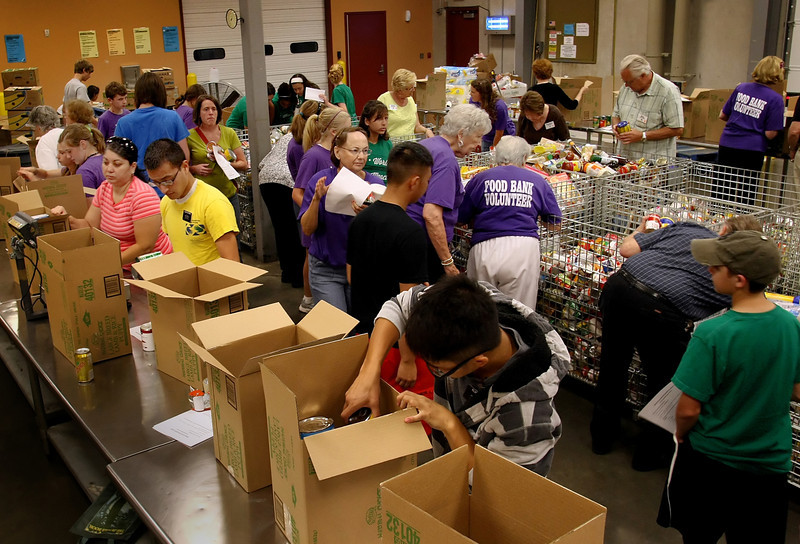 Volunteers at the NE Oklahoma Food Bankin Tulsa pack food boxes.