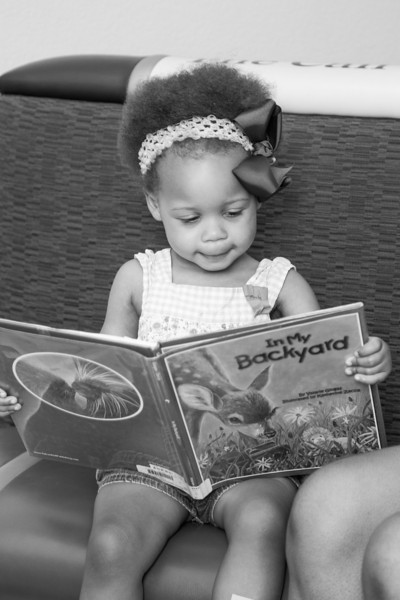 Corryn Johnson reads with her mother, LaKessha, at the Village Library.