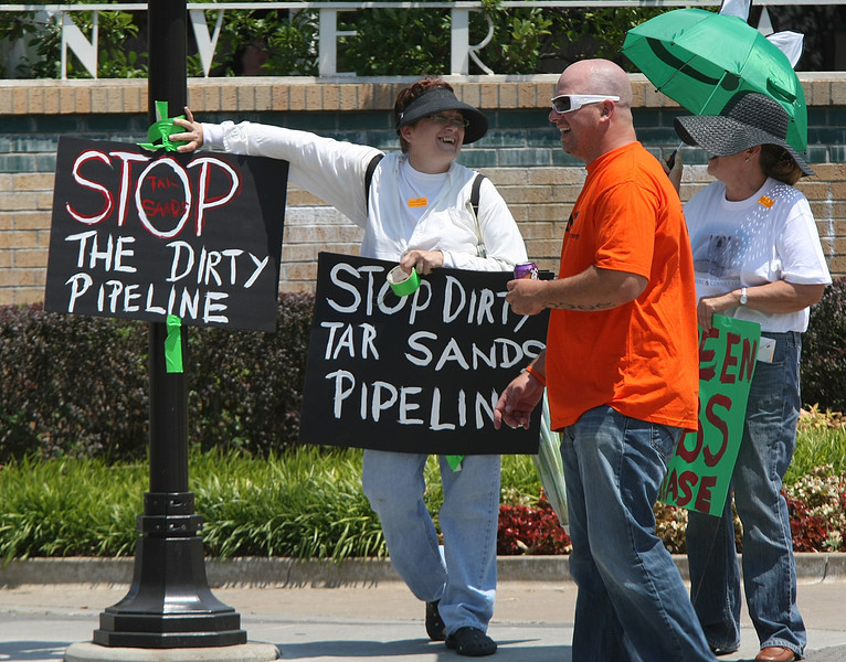 Members from both sides of a Keystone Pipeline demonstration share a laugh during the rally Wednesday in downtown Tulsa.