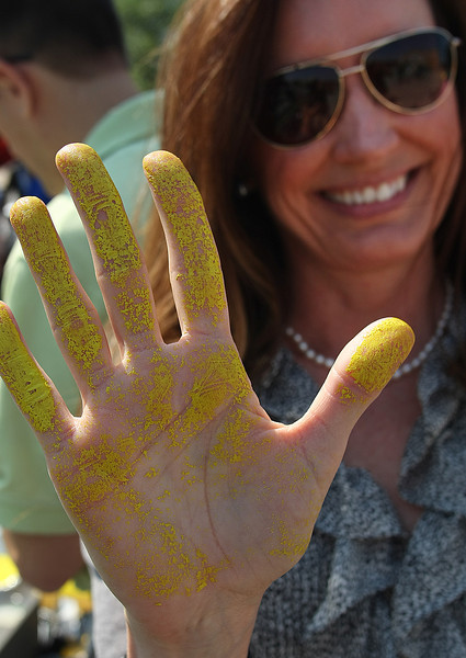 A supporter of the Hardesty Arts Center shows her painted covered hand she used to leave her palm print on the final beam that will be used in the construction of the building.