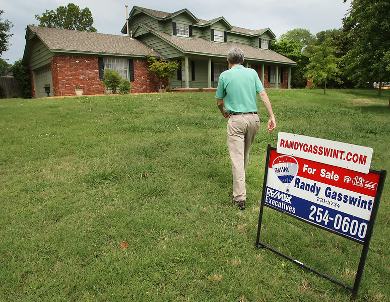 Realtor Randy Gasswint walks to his listing in South Tulsa after having set the yard sign.