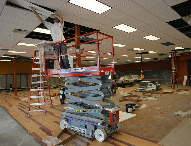 Workmen install celling tiles at the Green Acres Grocery store under construction in Jenks.