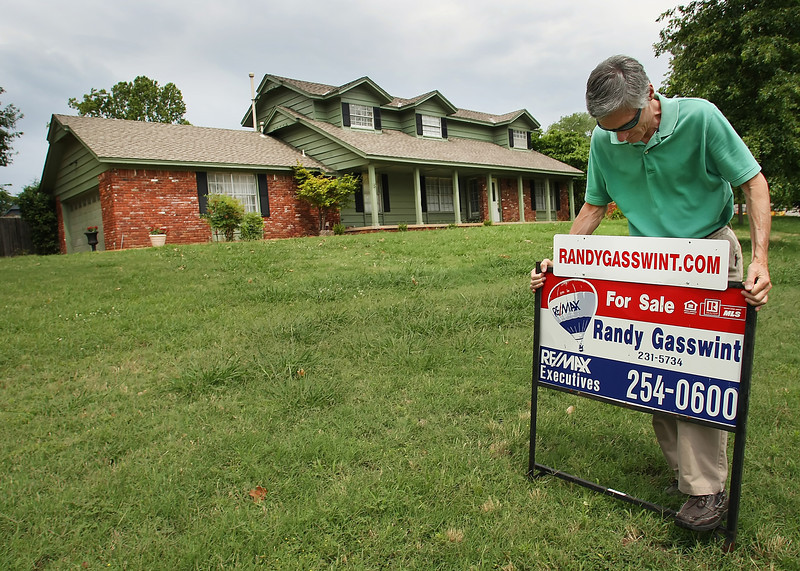 Realtor Randy Gasswint sets a yard sign at his listing in South Tulsa.