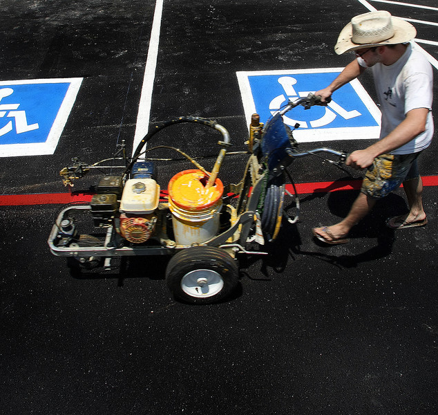 Spraying the red fire lane  stripe Justin Jiles of Action Striping puts the finishing touches on parking lot of the Green Acres grocery store in Jenks