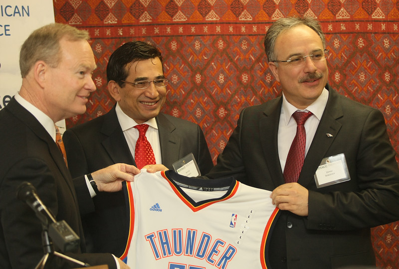 Oklahoma City Mayor Mick Cornett, left, and Kevin Sanders, president of the Oklahoma Turkish American Chamber of Commerce, far right, give a souvenier to Yunus Bekdemir and other visiting business people from Turkey on Thursday. PHOTO BY MAIKE SABOLICH