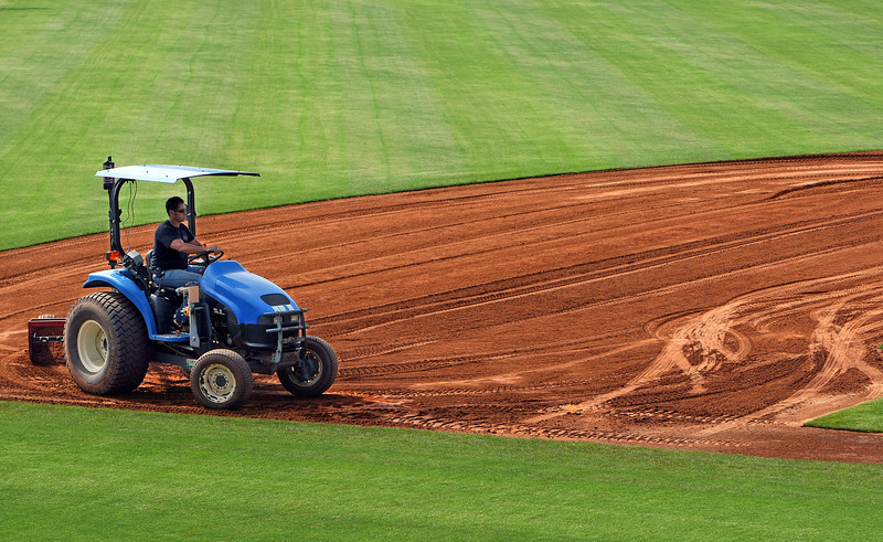 A workman grooms the infield soil along the third base line as final preparations are made before the Tulsa Drillers season begins in two weeks.