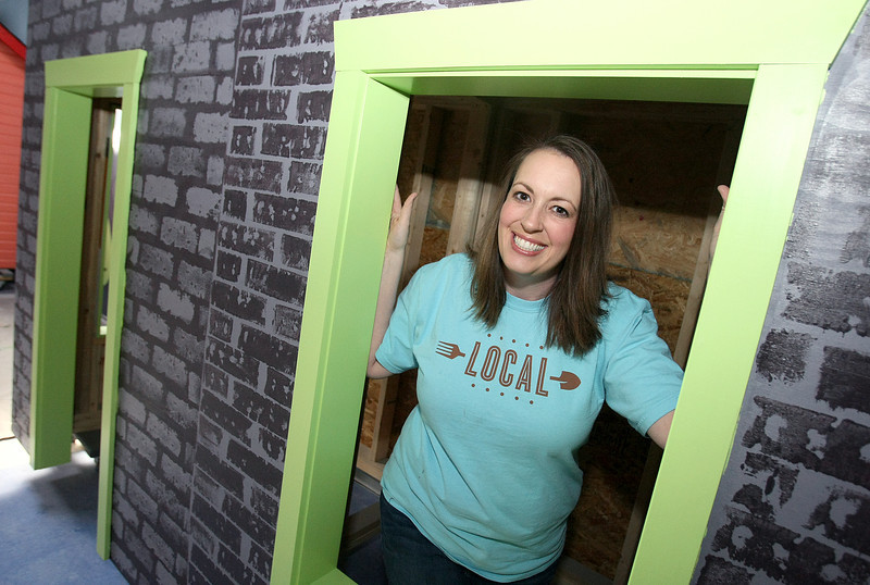 Abby Ckark, owner and manager at Local in Norman, peeks through the windows of a children's building at Localville. PHOTO BY MAIKE SABOLICH