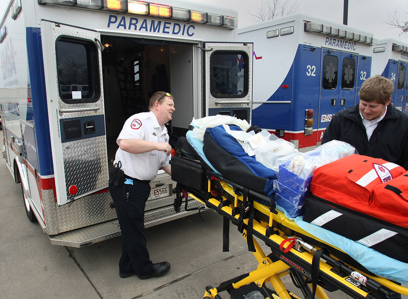 Paramedics Russell marin and Adam Ashford load their ambulance in Tulsa before heading out for their shift.