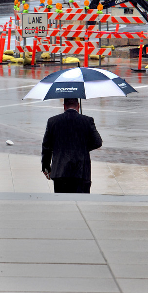 A pedestrian makes his way through the rain in downtown Tulsa Monday.