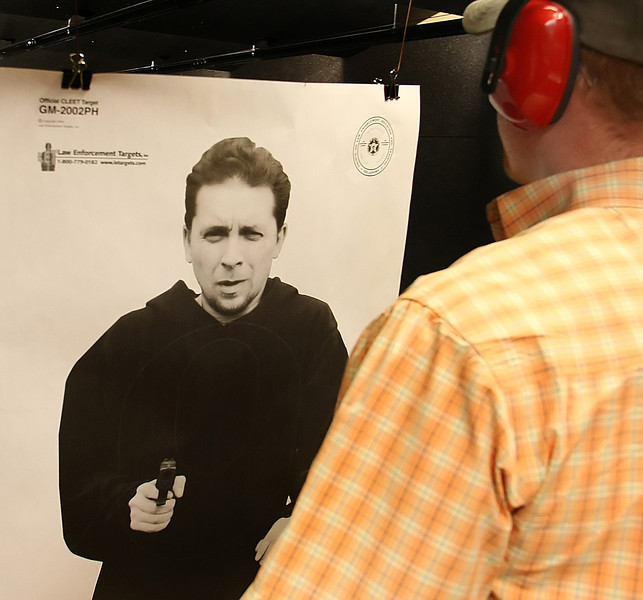 Cole Spencer examines a silhouette target before getting in a round of practice shooting at the C2 Shooting Center in Tulsa.