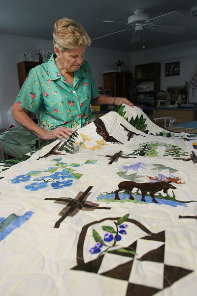 Neta Slayton pause with one of the quilts they have for sale on the website ETSY.com.