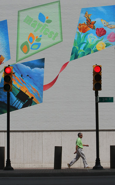 Pedestrians in downton Tulsa cross in front of a wall painted with Mayfest kites.  The art festival comes to tulsa May the 17th.