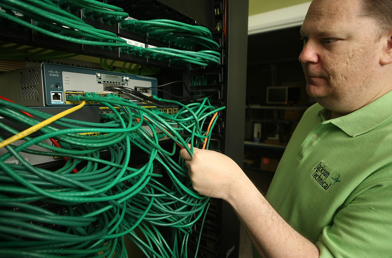 Tim jackson , President of Jackson Technical in Tulsa, trouble shoots a network switch at his companies office downtown.
