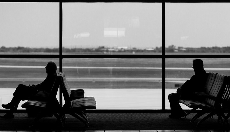 Two men wait for a flight at Will Rodgers International Airport.