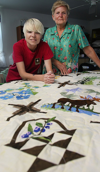 Trina Burfield and Neta Slayton pause with one of the quilts they have for sale on the website ETSY.com.