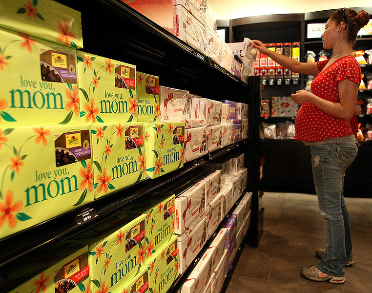 Expectant mother of twins Shanatha Moore browses Mothers Day gift packages of chocolates at the Russell Stover Candy store in South Tulsa.