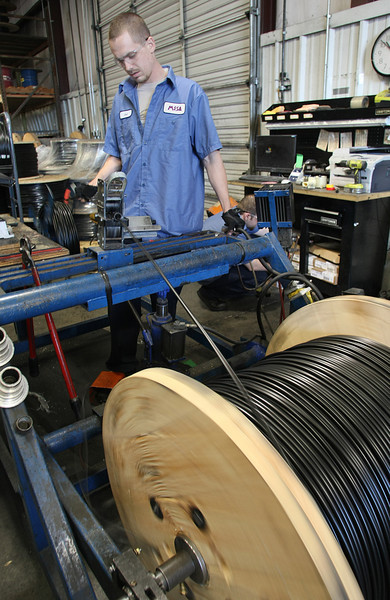 Mesa Cathodic Protection employee Joe Smalley winds cable use to connect an anode used to control corrosion in pipelines.