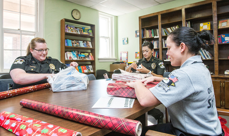 Kelli Bruemmer, Belen Rodrigaz and Lacey Spanier, with the Oklahoma County Sheriff's department, wrap gifts for needy children at Sunbeam Family Services.