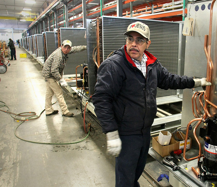 Workmen assemble industrial Air-conditioning unit at the AAON plant in Tulsa.  AAON fell back to earth with a 7-percent increase in third quarter net income to $6 million.