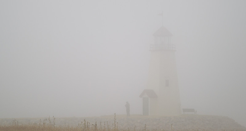 A thick fog at Hefner lake. From Louise on the Lake the light house and the person standing in front of it can barely be seen.