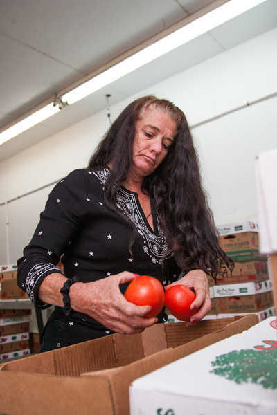 April Glass inspects and counts tomatoes at Buddy's Produce in Midwest City.