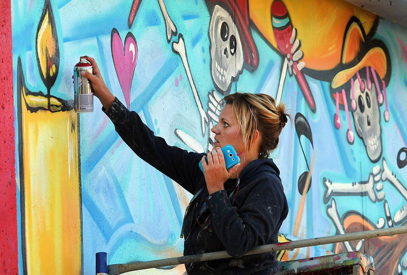 Laura Thompson paints a wall mural as part of a Day of the Dead competition sponsored by Living Arts of Tulsa.