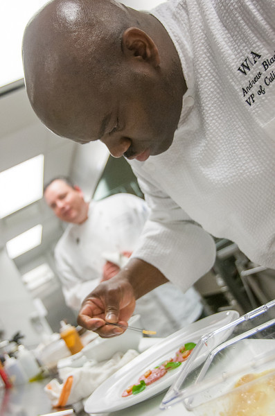 Chef Andrew Black carefully prepares a dish on the opening day of Vast atop the Devon tower.
