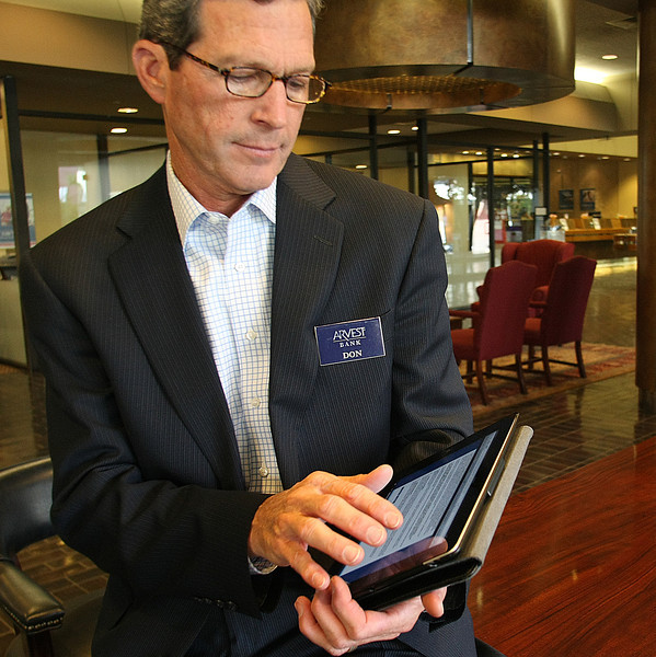 Don Walker, President & CEO at Tulsas Arvest Bank, uses an IPAD to demonstrate an application used to bank using mobile platforms.
